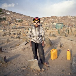 An Afghan boy is seen with a Minnie Mouse face mask in a local cemetery in Kabul, Afghanistan on Oct. 10, 2006. Photo by Ziyah Gafic/VII Network