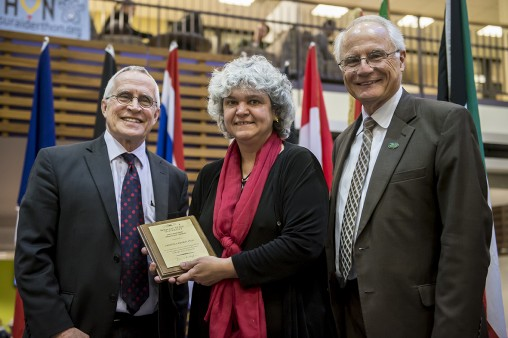 Cristina Redko, assistant professor of community health, center, accepted the International Education Award from Stephen Foster, University Center for International Education associate vice president, left, and Wright State President David R. Hopkins.