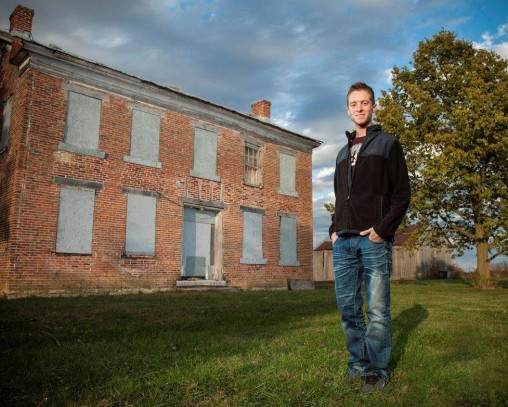 Connor Keiser in front farmhouse
