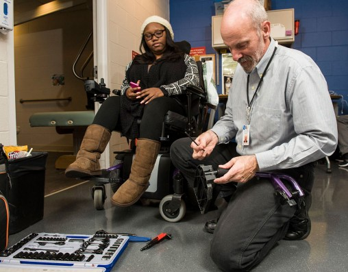 Jim Voisard, an assistive technology professional at Numotion, fixing a wheelchair pedal for Wright State student Dominique Jenkins.
