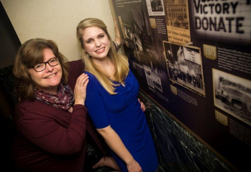 Shelby Dixon, right, a graduate public history student at Wright State, and Sue Stevens, Victoria's vice president of marketing and communications, with part of the pictorial timeline at Victoria Theatre. (Photos by Chris Snyder)