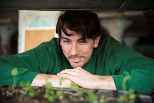 Volunteer Graham King, who graduated from Wright State in 2015, looks at seedlings.