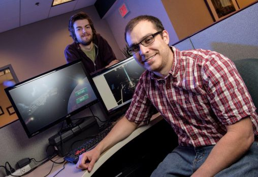 Noah Schroeder, right, assistant professor of education technology and instructional design, is working with several students, including Kenneth Deffet, to design a video game that can be used as teaching tool in classrooms. (Photo by Erin Pence)