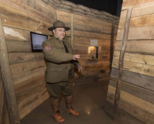 Dressed as a YMCA volunteer from World War I, Paul Lockhart shows off the exhibition's replica war trench. (Photo by Erin Pence)
