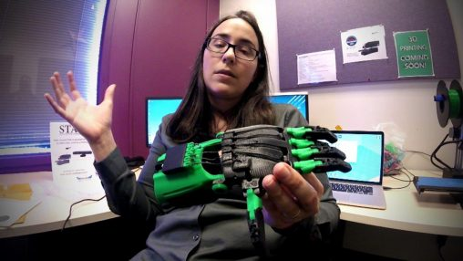 Ashley Hall, assistant professor of English and communication, holds an artificial hand students in her Digital Rhetoric class created on a 3-D printer. (Photo by Kris Sproles)