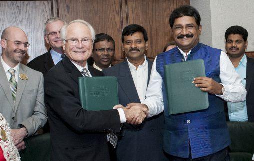 Wright State President David R. Hopkins and Ganta Srinivasa Rao, the minister for human resources development of Andhra Pradesh, shake hands after signing a memorandum of understanding.