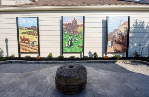 Katelyn Puthoff's mural depicts a farming scene, Minster's original log cabin Catholic church and a street scene from the early 1900s.