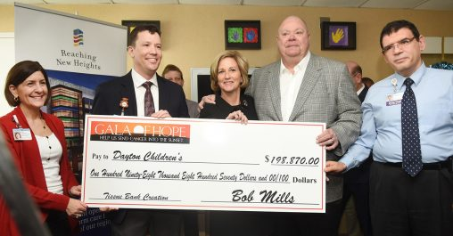 Barbara and Bob Mills, Gala of Hope Foundation co-founders, presented a giant check to pediatric neurosurgeon Robert Lober, second from left, at a ceremony at Dayton Children's Hospital.