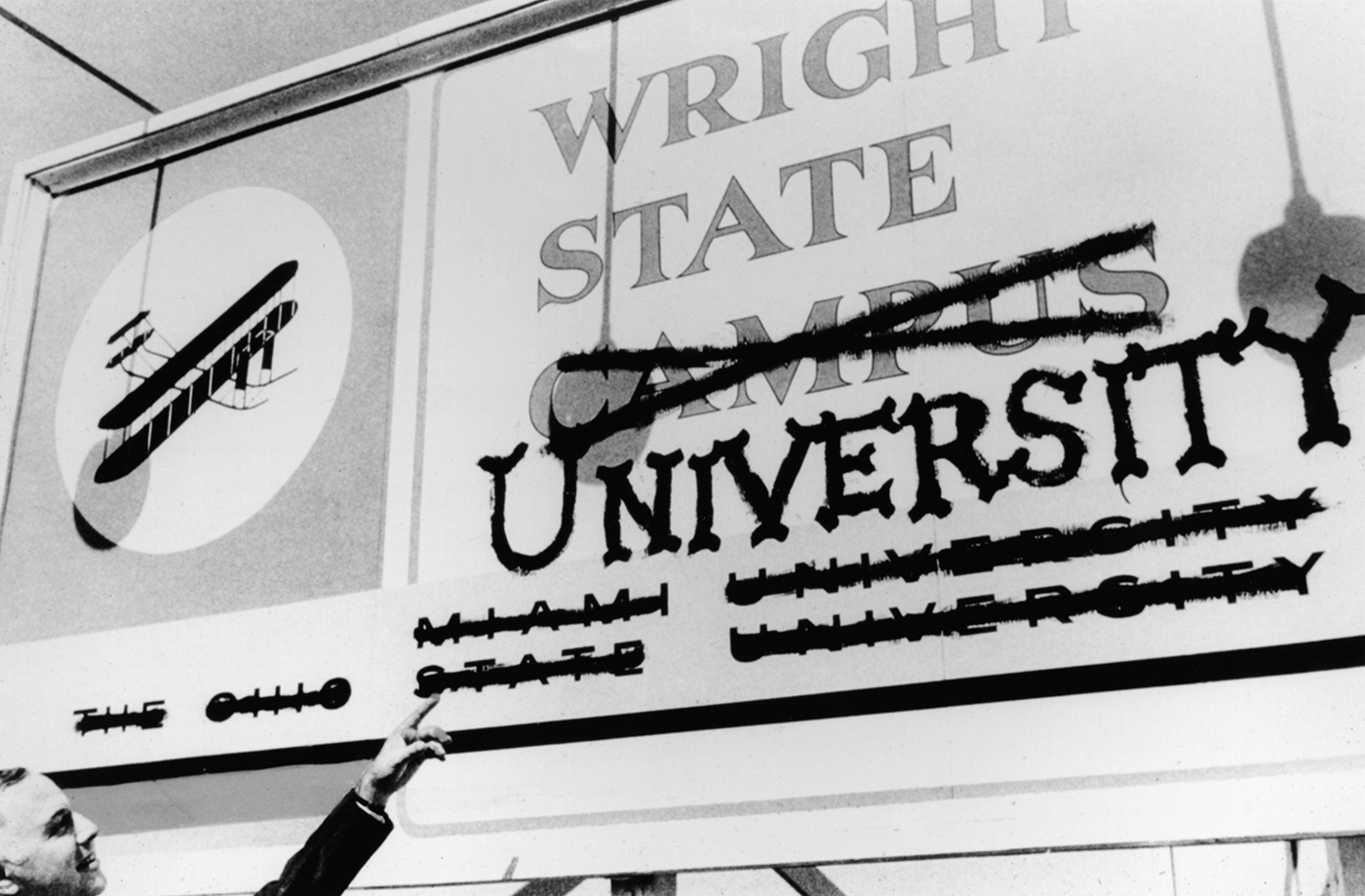 Brage Golding, Wright State's first president, pointing at the former Wright State Campus sign.