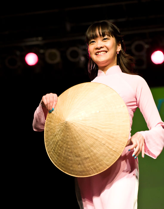 Photo of a smiling young woman in a Vietnamese dress carrying a large hat.