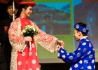 "Photo of a young man ""proposing"" to a young woman, both dressed in Asian clothing."