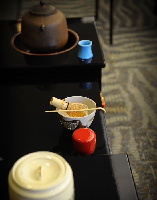 Photo of china cups and a teapot on a low table.
