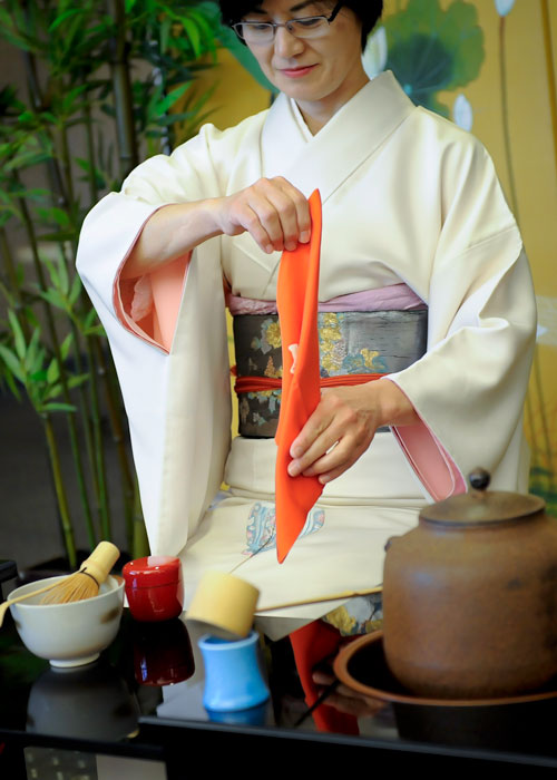Photo of the tea mistress folding an orange cloth napkin.