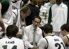 Picture of head basketball coach Billy Donlon instructing his players on the court as they huddle around him.