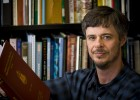 Photo of professor Thomas Rooney holding a book in front of a book case.