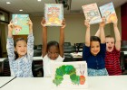 Photo of four kids smiling holding books over ther heads.