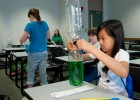 Photo of a girl dumping green liquid from one two liter bottle to another.