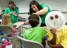 Photo of pre-college campers making and wearing their own masks made from paper plates.