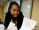 Photo of girl holding finger print strips and a wanted poster she created in the forensic Science pre-college camp.