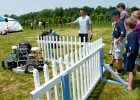 Photo of robotic lawn mower mowing grass near a white picket fence during the competition.