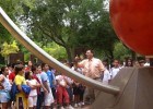 Photo of Dr. Cambronero speaking to a group of children in front of the Sun sculpture.