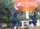 Photo of two workers installing the Sun sculpture.