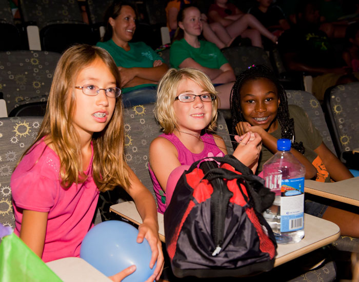 """Photo of Stella Joly, Kaylee Gleason and Olivia James watching the """"Discovery Video"""" camp's highlights of the week."""