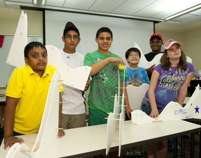 "Photo of six pre-teen students showing off their roller coasters they made in the ""Investigation STEM"" pre college camp."