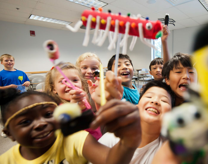 Photo of many kids showing off their toys they made for the camera.