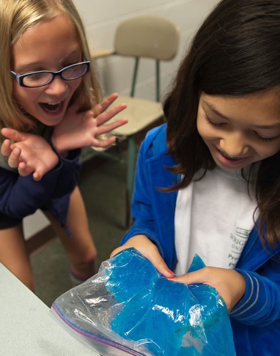 Photo of two girls squishing a bag with a blue gelatinous substance.