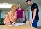Photo of a female student demonstrating to two other students how to use a smartpen.