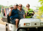 Photo of a volunteer and two parents on a golf cart during move-in day.
