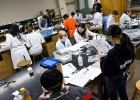 Photo of a room full of students in lab coats