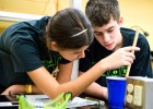 Photo of two students measuring something with at ruler