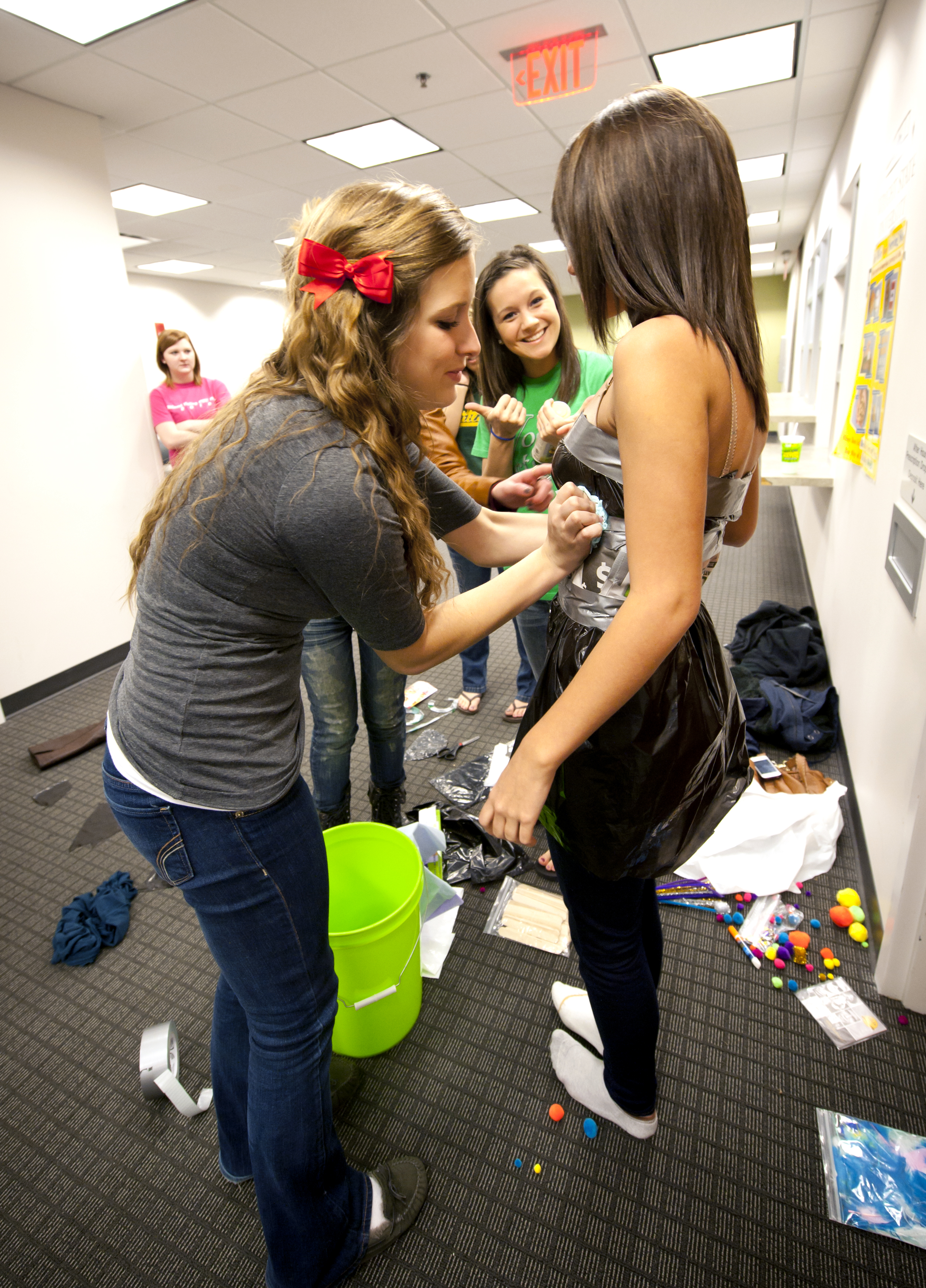 Photo of one student putting duct tape and newspaper on another student.