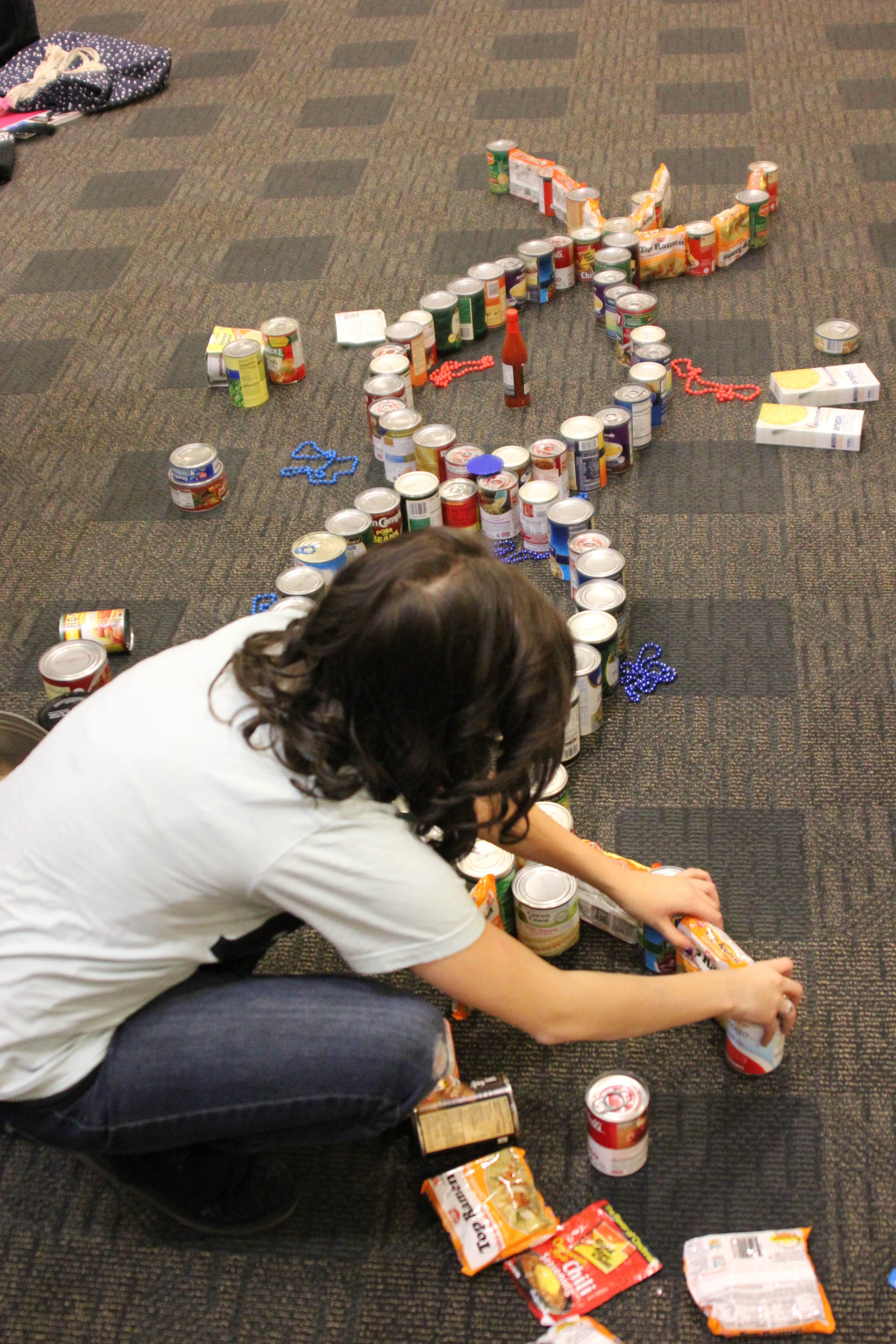 Photo of student making a sculpture out of canned goods.