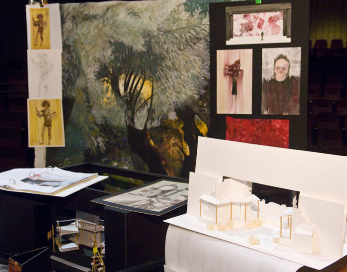 Photo of a display of set design sketches and models.