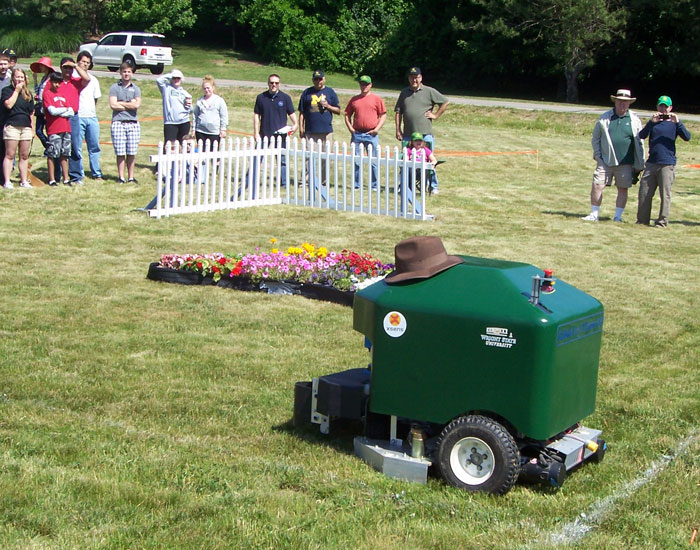 Photo of the lawn mower with a flowerbed and fence