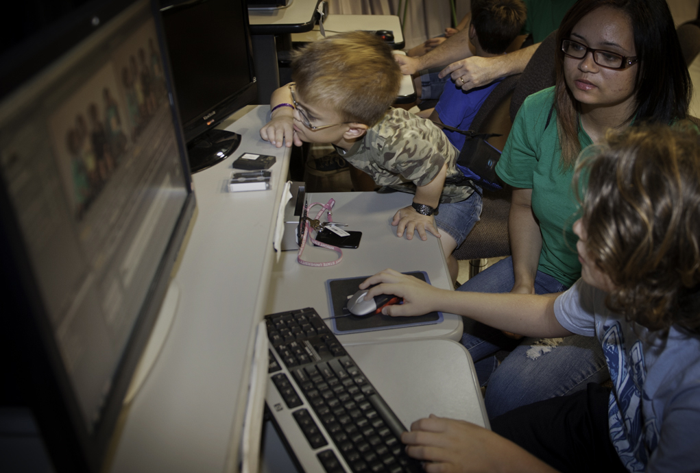 Photo of a few pre-college camp students working at a computer.