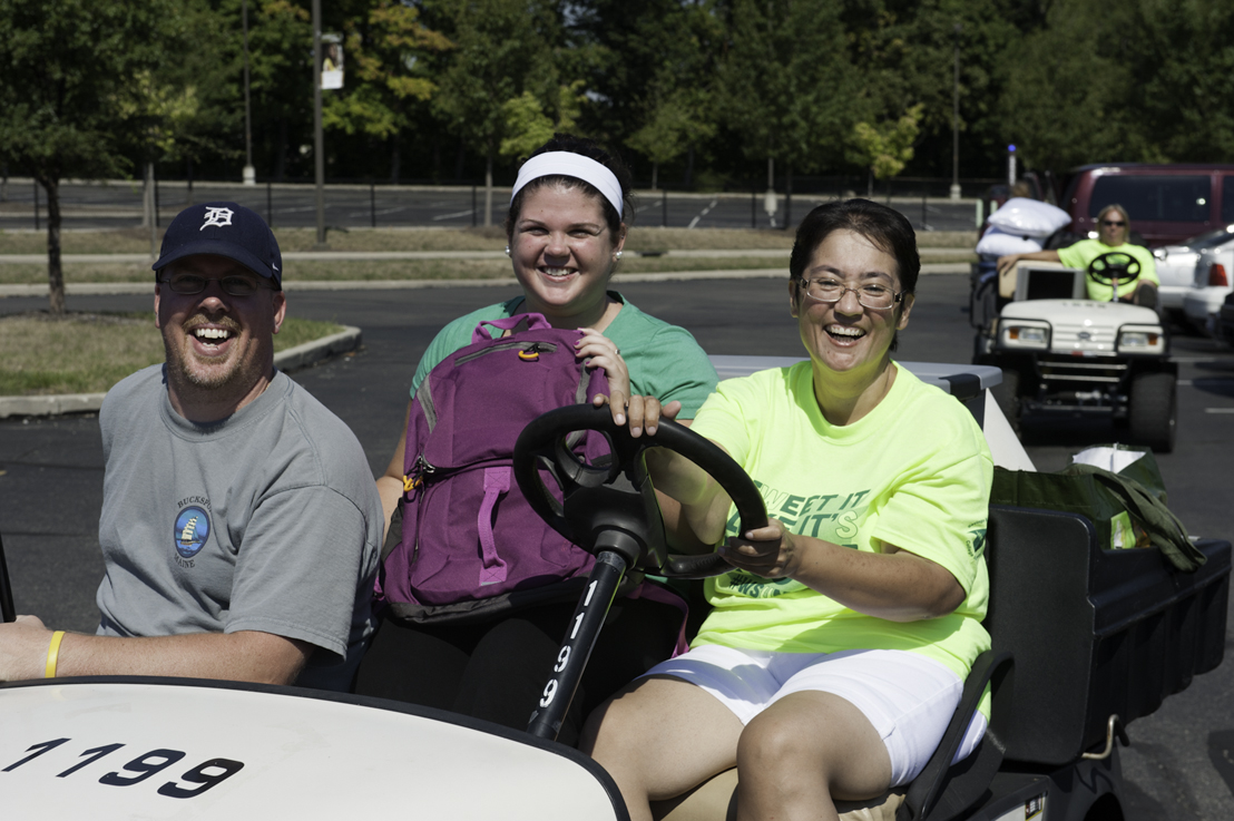 Photo of a Wright State freshman, her father and a volunteer on a golf cart.