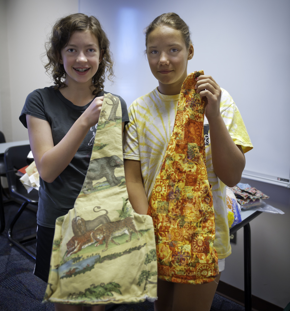 Photo of pre-college students Caroline Celaney (left) and Maryana Petrova showing their work from the Cretive Sewing class.