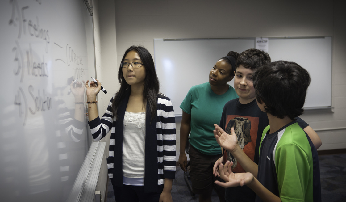 Photo of Ms. Jennille Love (green), James Durbin (green and black) Christine Kim (stripes) and Grant Crawford (red and black) in the Talk About It class where students learned about how to constructively deal with conflict and disagreement.