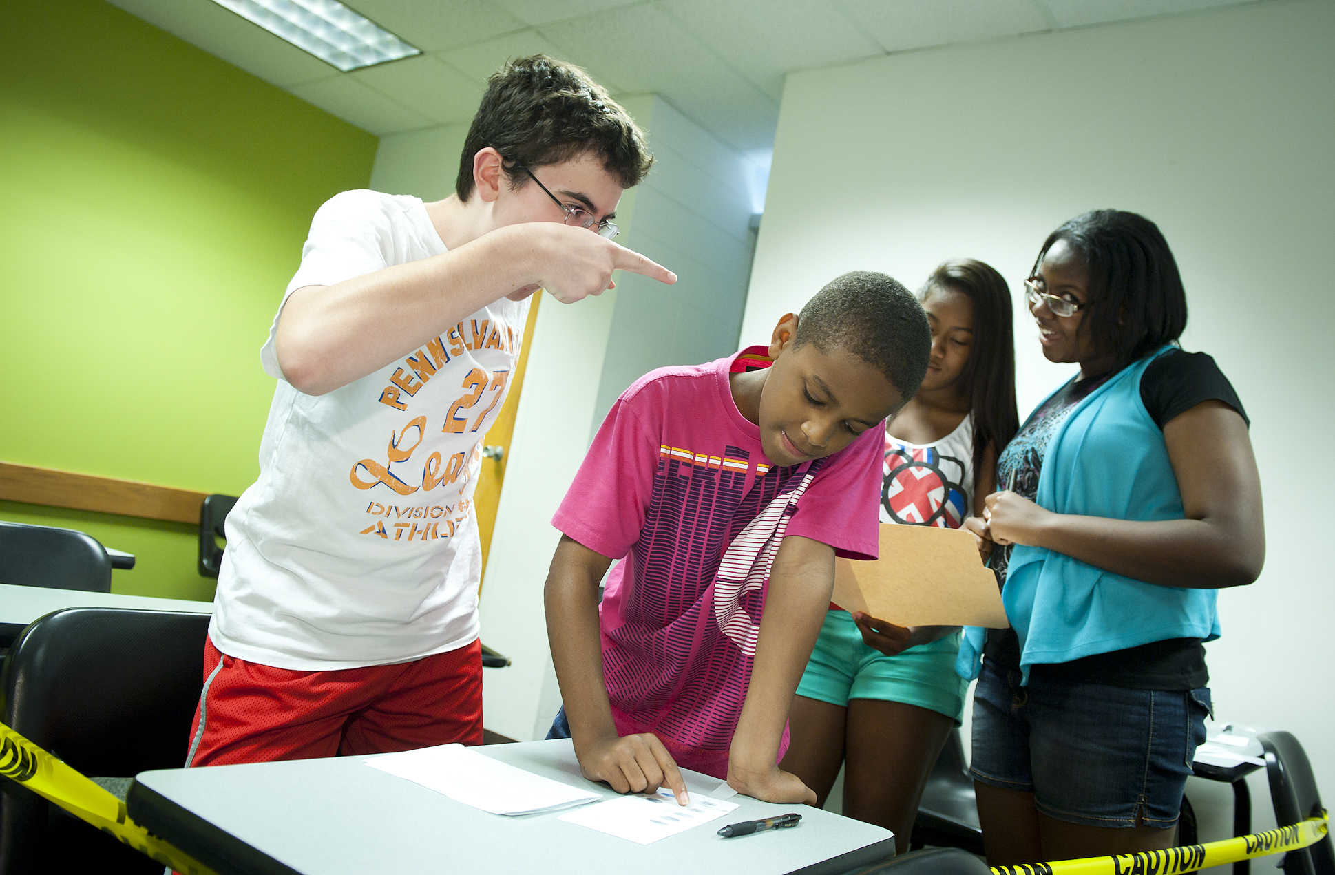 Photo of Tucker Bullock, Elijah Sanders, Kri'Shawn Fleming and Dominique Schmidt solving a crime in Camp Odyssey's Forensic Analysis.