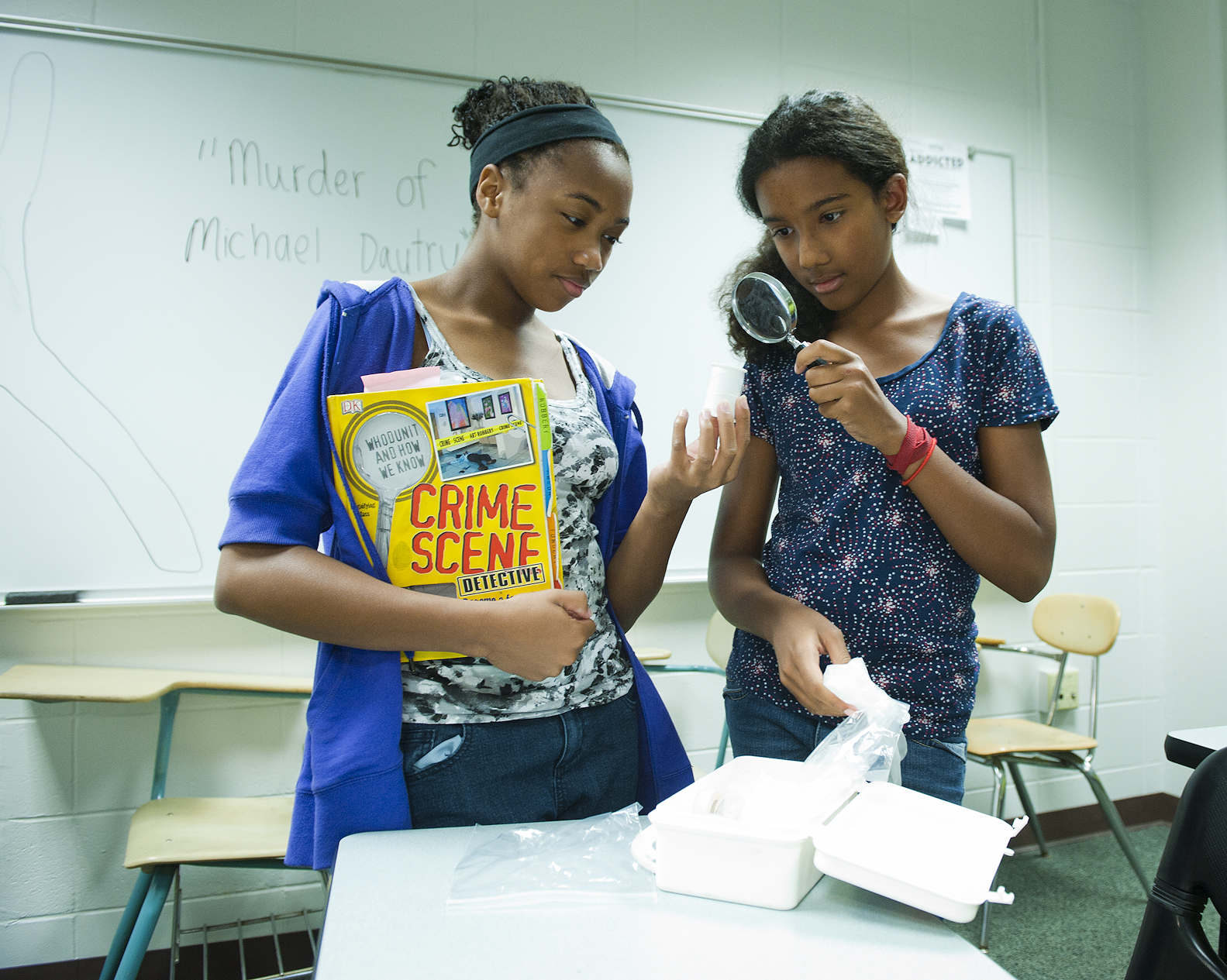 Photo of Kaelyn Sanders and Ayanna Madison investigating some tiny evidence in Forensic Analysis Camp.