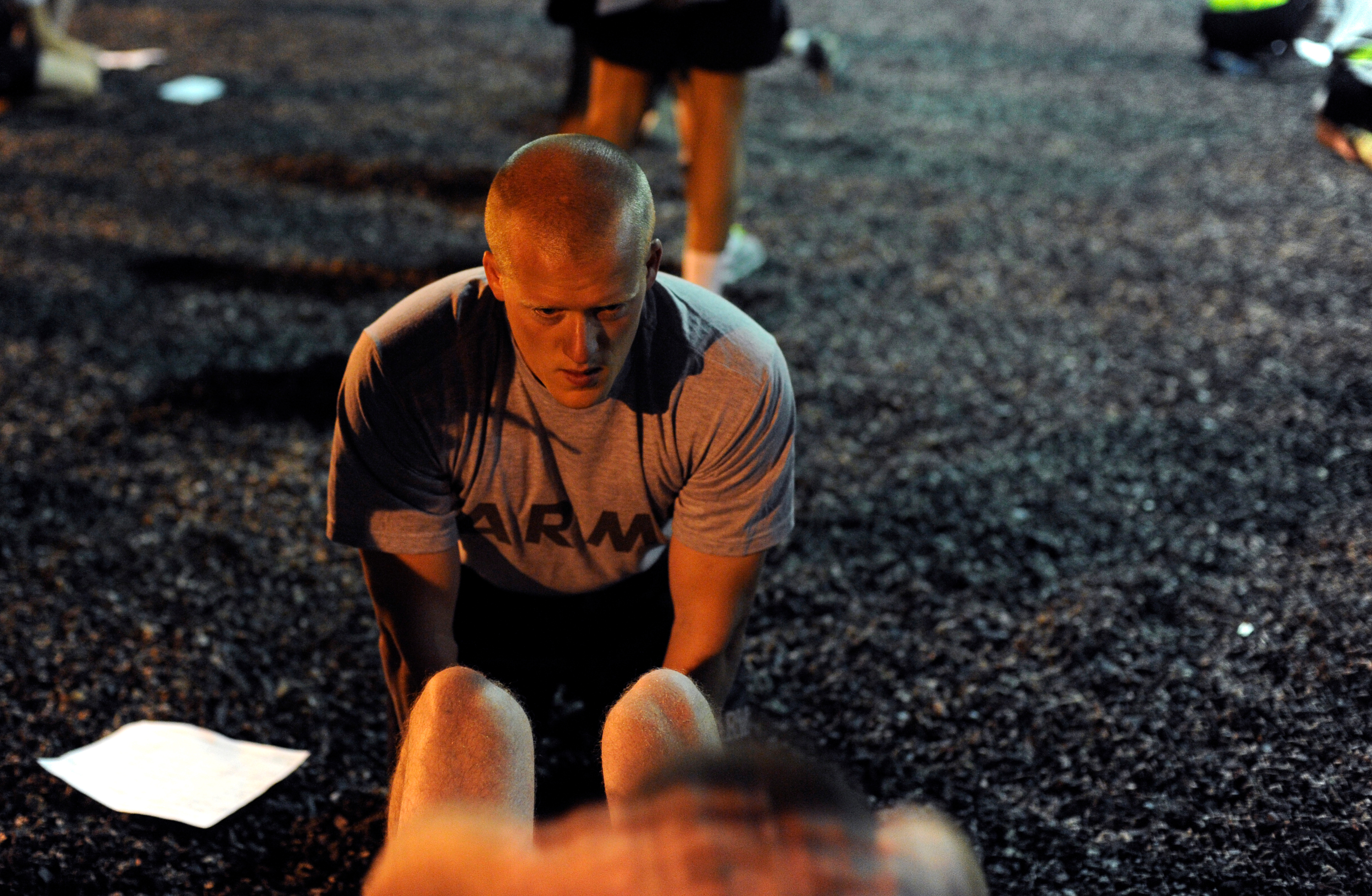 Photo of Brian Bolibrzuch helping a fellow cadet perform situps during the Leader's Training Course.