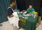 A photo of an employee visiting at a table during the the 2011 Health and Benefits fair.