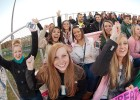 Photo of students cheering in the stands at the soccer field.