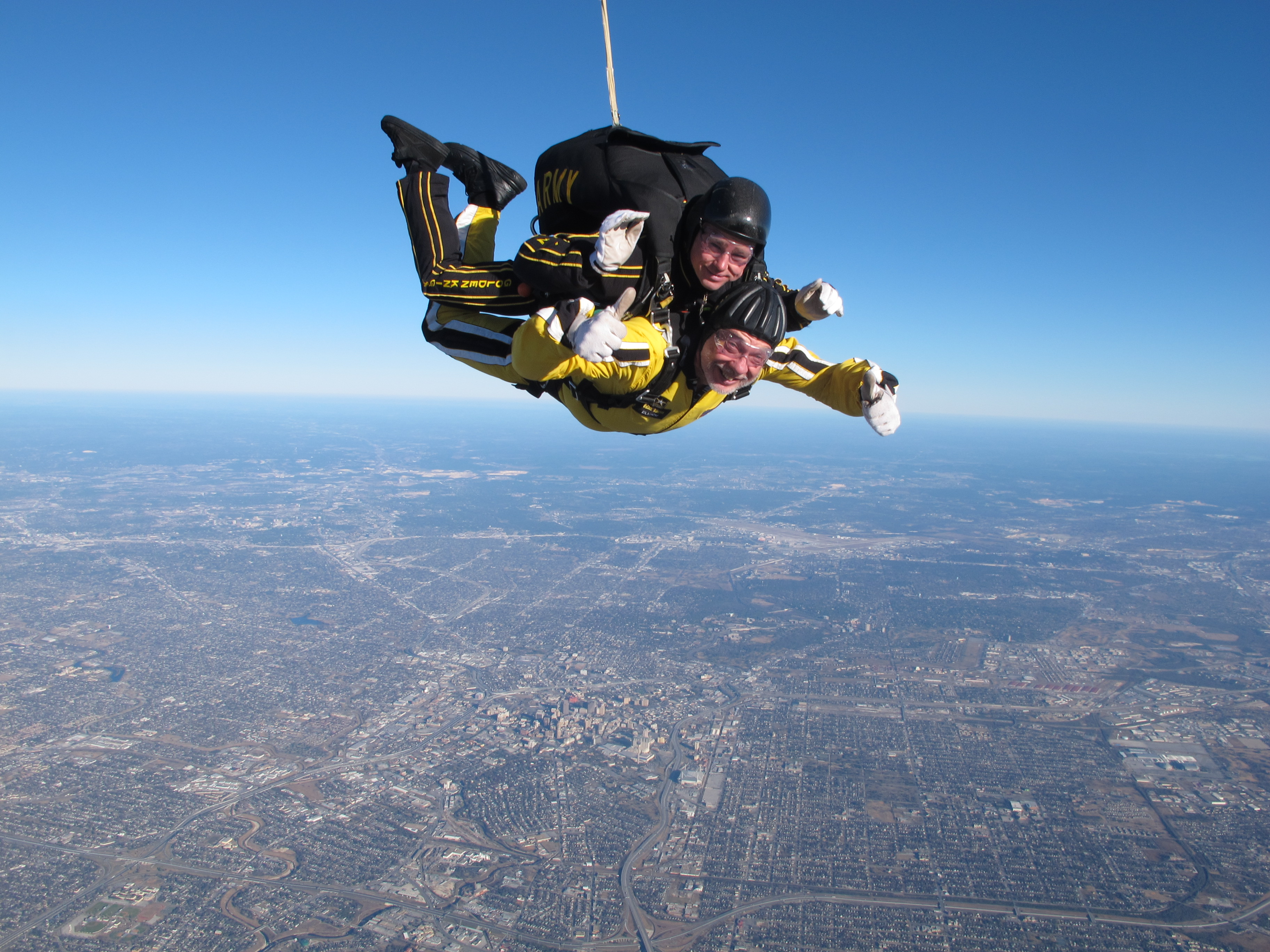 Photo of Wright State's Herb Dregalla (in yellow suit) skydiving with an Army Golden Knight