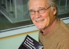 Photo of political science professor Charles Funderburk with the book Political Corruption in Comparative Perspective, which he and six other faculty members partnered to produce.