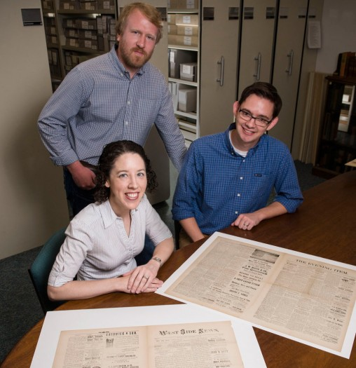 Lisa Rickey, Ryan O'Grady and Andrew Harris with several Wright brothers newspaper issues.